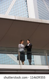 Two Businesswomen Having Discussion Outside Office Building