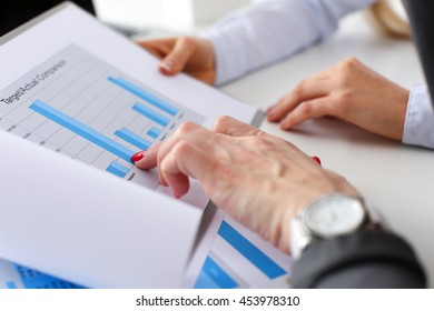 Two businesswomen hold in hands graph solving and discussing problem closeup. Fresh view, review situation, look at new angle, professional training, white collar, investment and finance concept