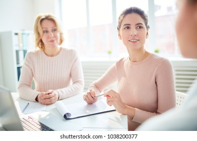 Two businesswomen listening to their associate during discussion of financial information