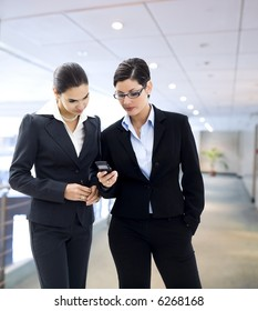 Two businesswomen looking at mobile phone screen on the office corridor.