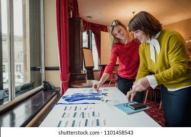 Two businesswomen looking for their name badges on the table before the conference starts.