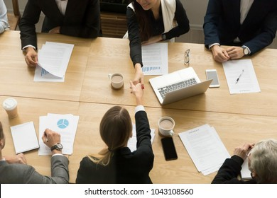 Two businesswomen shake hands at team meeting, female partners handshaking making deal signing contract, welcoming new partner at group negotiation, women power in business concept, top view overhead