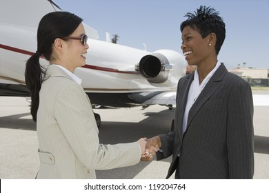 Two businesswomen shaking hands in front of private plane