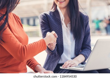 Two businesswomen shaking hands  in outdoor. Finishing successful business negotiations