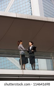 Two Businesswomen Shaking Hands Outside Office Building