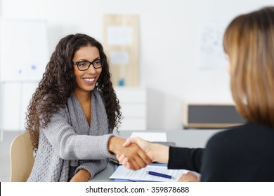 Two businesswomen shaking hands over a desk as they close a deal or partnership, focus to a smiling young African American lady