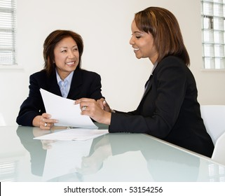 Two businesswomen sitting at office desk having meeting and discussing paperwork.