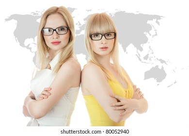 Two businesswomen standing together back to back against world map