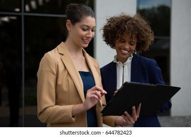 Two businesswomen using digital tablet near office building