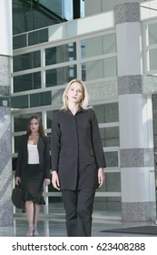 Two businesswomen walking out of building