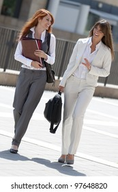 two businesswomen walking outdoors while talking