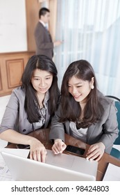 Two businesswomen working on the laptop while businessman phone on background