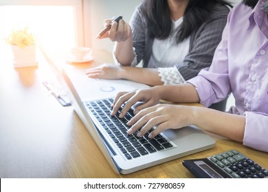 Two businesswomen working together on laptop in office