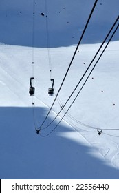 Two cable cars full of skiers crossing over at the mid way point with a glacier below