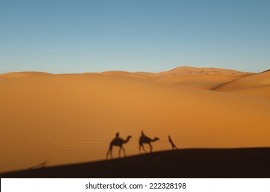 Two Camel Riders Have Their Shadows Cast on Sand Dunes in Morocco