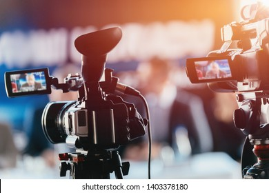 Two cameras recording presentation at press conference, blurred speakers wearing suits background, live streaming concept - Shutterstock ID 1403378180