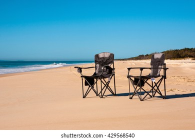 Two Camping Chairs On A Sandy Island Beach