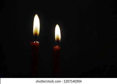 Two candels burning in the dark