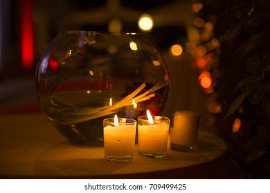 Two candles burning in the darkness in front of a sphere transparent vase with flowers inside