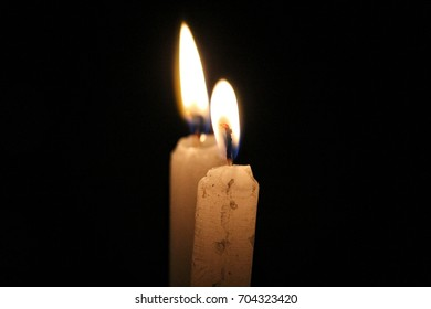 Two Candles in flames with black background
