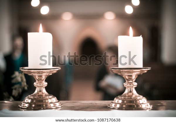 two candles on golden candleholders in a christian church after holy mass