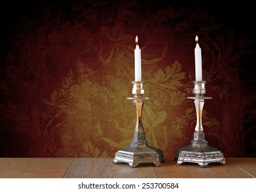 two candlesticks with burning candles over wooden table and vintage background