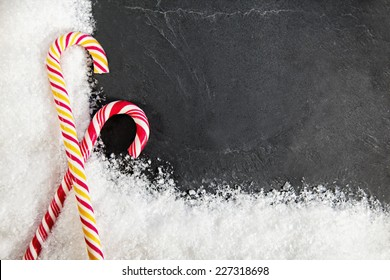 Two Candy Canes On Black Background With Snow Around. Copy Space