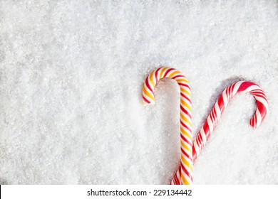 Two Candy Canes On Snowy Background. Copy Space