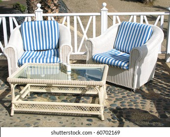 Two cane armchairs and a table