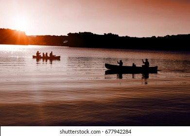 Two canoes with people on the lake for late evening fun