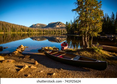 two canoes sit on the shore of a calm mountain lake