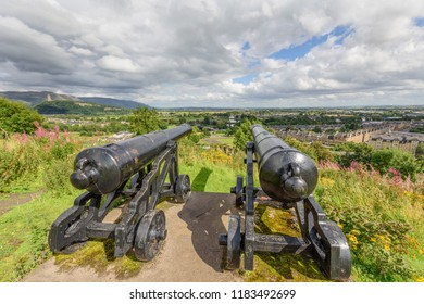 Two canons on Mote Hill close to Stirling Castle with Wallace Monument in distance in Scotland.