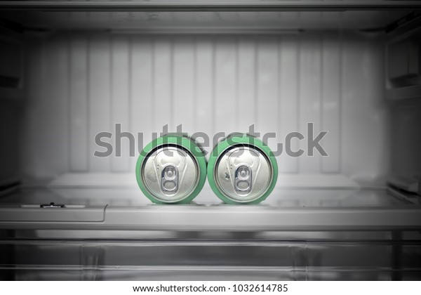 Two cans of beer lie in an empty fridge. Dewy cans with beer on a shelf in the refrigerator.