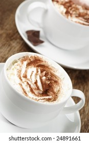 Two cappuccino coffees topped with fresh cream and dusted with chocolate powder