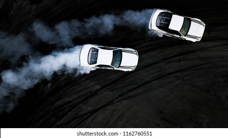 Two car drifting battle on asphalt street rad race track, Race car drift performance view from above, Car drifting, Automobile and automotive drift car with smoke from burning tire on speed track.