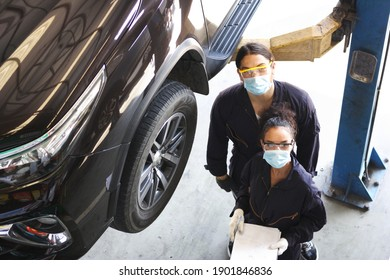 two car mechanic on protective mask anti coronavirus or covid19 ,  they are fixing  and service maintenance of industrial to engine repair, for transport automobile automotive