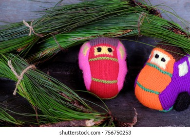 Two car transport pine tree for Xmas decoration, knitted colorful cars move on wooden make funny Christmas background