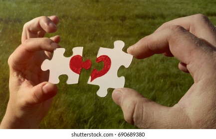Two cardboard puzzles with a painted red heart are held in the hands on a background of green grass. love.