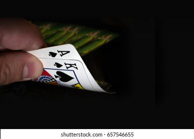 Two cards king and ACE of spades on a black background in the player's hand. Luck in the game of blackjack.