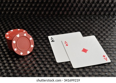 Two cards with red poker chips on a black background