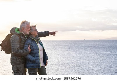 Two carefree senior people with backpack on their back enjoys the hike on the ocean cliffs looking at the horizon over water viewing the profile of an island and a ship.