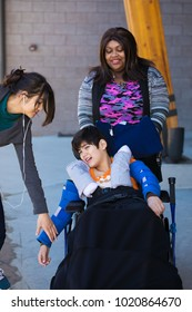 Two caregivers helping take care of disabled eleven year old boy in wheelchair. Biracial, Asian Caucasian child. Has cerebral palsy.