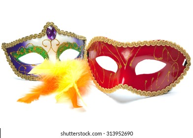 Two carnival masks in purple, green and red and yellow with feathers
