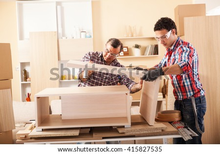 Two Carpenters Working At Location.Repairing Furniture.Assembling Table.