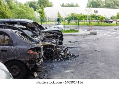 Two cars after the fire. Two burned out cars with an open hood. Arson, burnt car