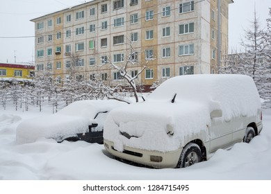Two cars covered with snow during a snowfall. Around the snowdrifts. Snow on roofs, windshields and windows of cars. In the background panel building. Cold winter weather. Magadan, Far East of Russia.