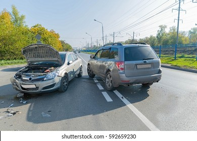 Two cars crashed on the road in autumn time.