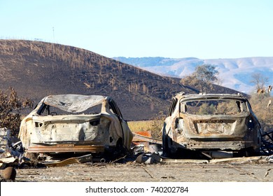 Two cars parked off the road, burned in the North Bay firestorm. Charred landscape in the background.