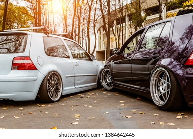 Two cars white blue and purple want to take one parking space. Parking problems in the city. Parked tightly to each other. Snuggled bumper. Low tuned cars with forged custom wheels