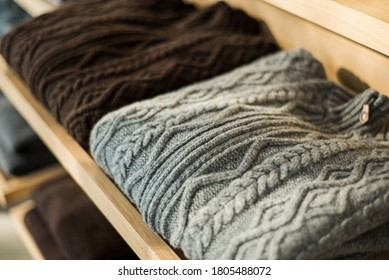 Two cashmere cardigans in gray and brown. Woolen cardigans on the shelf. Cashmere cardigans in men's wardrobe